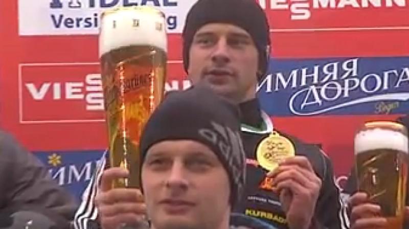 """Martins Dukurs ar kausu Altenbergā  (priekšplānā - Tomass Dukurs) Foto: no """"bobskeletv"""" video"""
