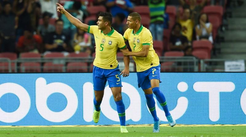 Brazīlijas izlases futbolisti Kazemiru (no kreisās) un Rišarlisons priecājas pēc vārtu guvuma. Foto: AFP/Scanpix