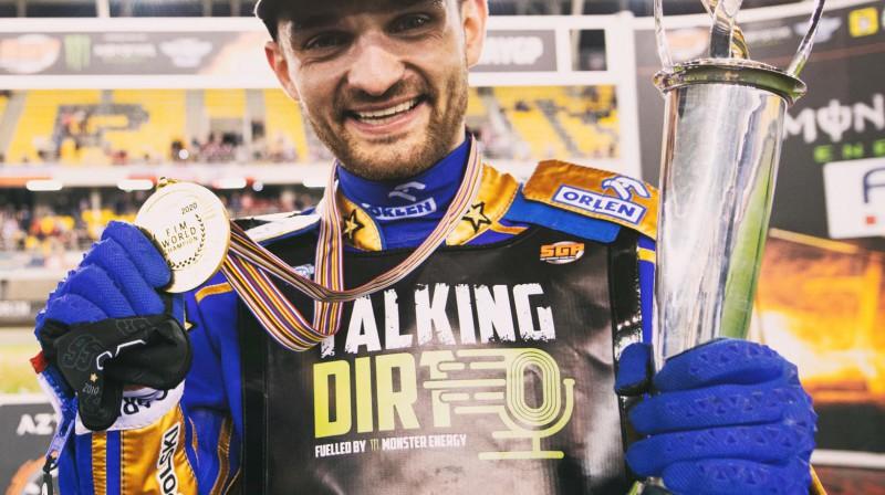 Divkārtējais pasaules čempions spīdvejā Bartošs Zmaržliks ar trofeju un medaļu.